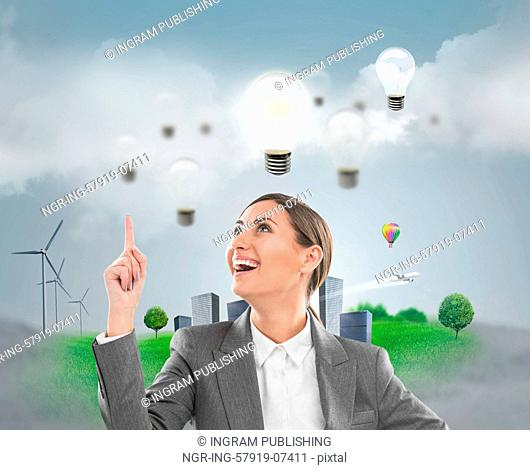 Ecology ideas concept. Businesswoman standing in front of cityscape with lamp overhead