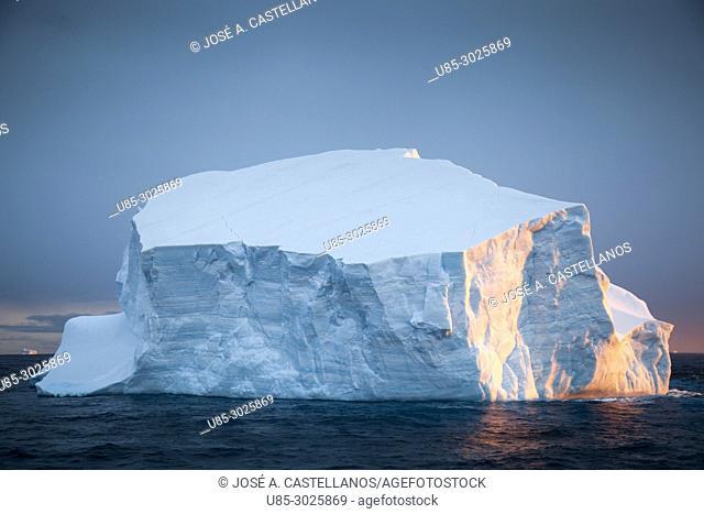 Antarctica. Iceberg near the Antarctic continent, sunset reflection on ice