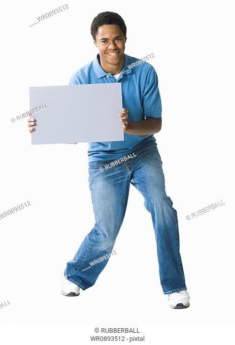 Portrait of a teenage boy holding a blank sign