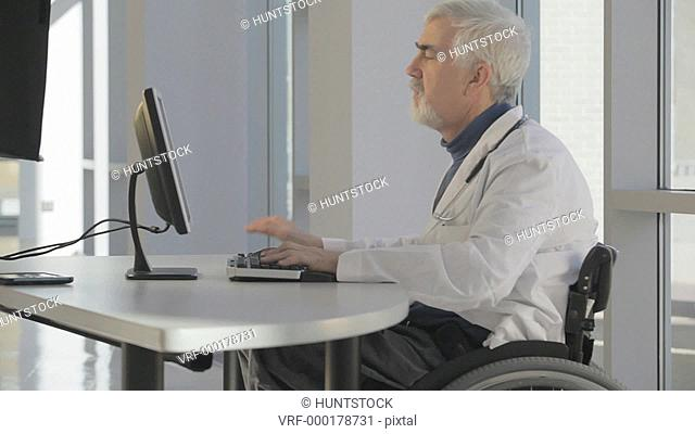 Doctor in wheelchair with Muscular Dystrophy using the hospital computer