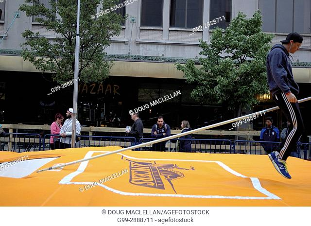 A male pole vault university athlete straddles a pole after his warm up attempt during a downtown exhibition sponsored by a university