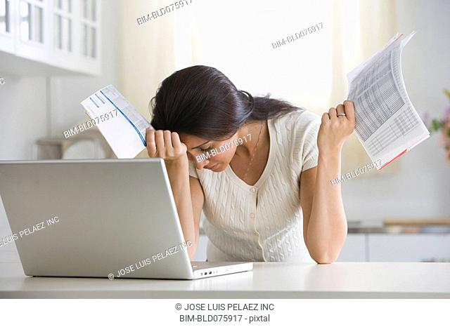 Overwhelmed woman holding bills in front of laptop