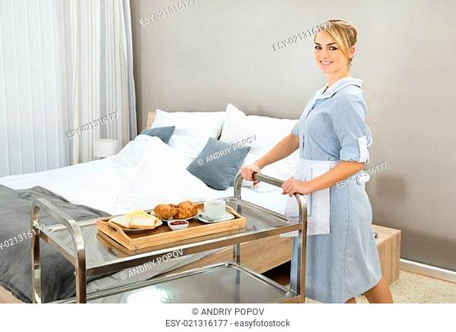Young Happy Woman Pushing Trolley With Breakfast In Hotel Room