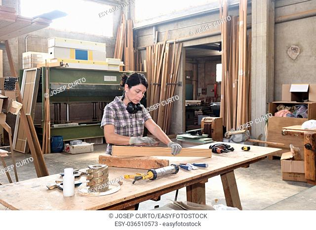 a woman working in a carpentry workshop, sand