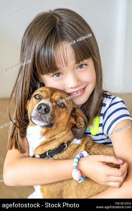 Portrait of eight year old girl hugging her pet dog