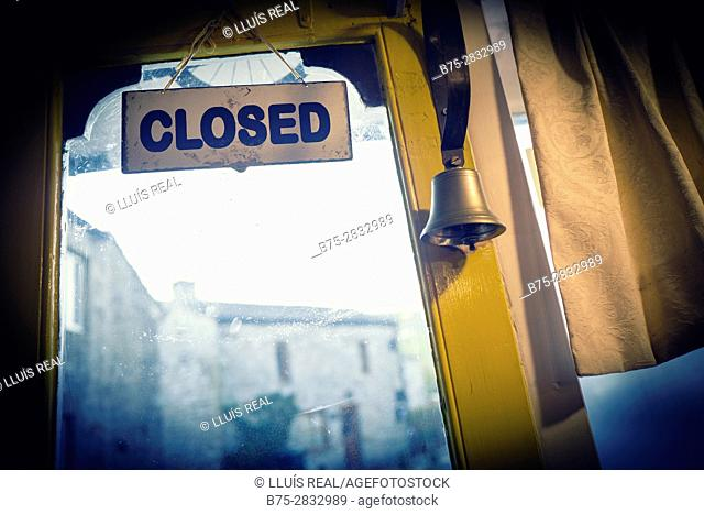 """Back of a door with a """"CLOSED"""" sign hanging a bell in an antique shop. Skipton, North Yorkshire, England, UK"""