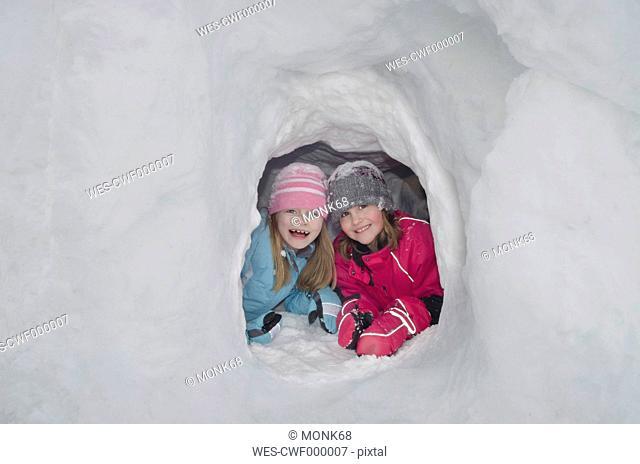 Austria, Girls in igloo, smiling