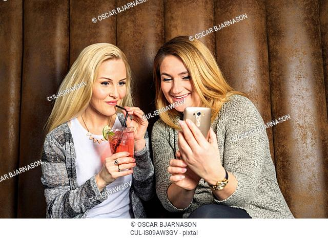 Friends in bar drinking cocktails looking at mobile phone smiling
