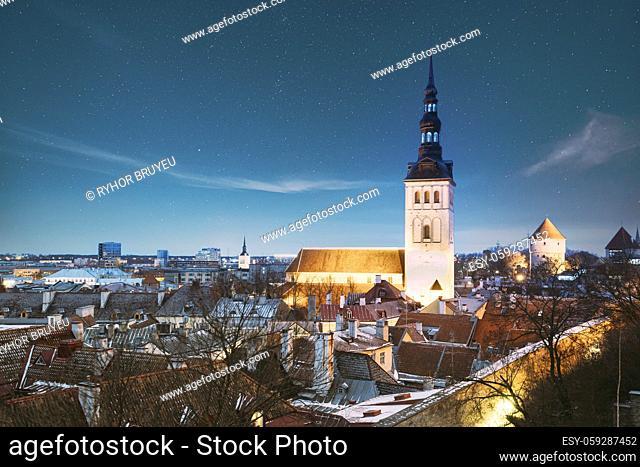 Tallinn, Estonia. Night Starry Sky Above Traditional Old Architecture Skyline In Old Town. St. Nicholas Church - Niguliste Kirik In Winter Evening Night