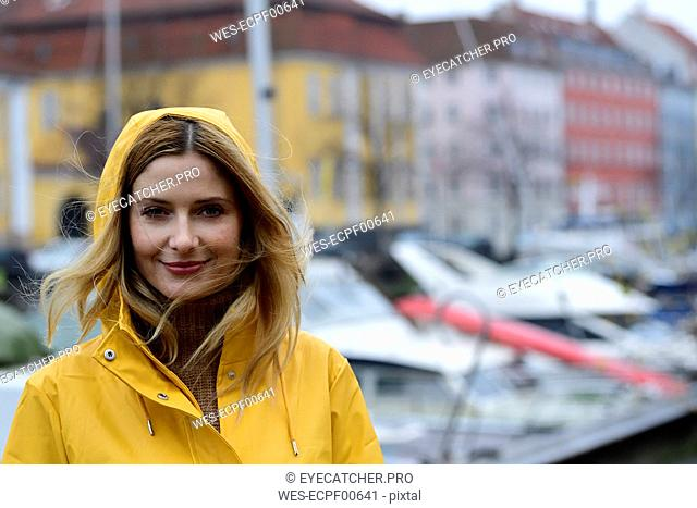 Denmark, Copenhagen, portrait of smiling woman at city harbour in rainy weather