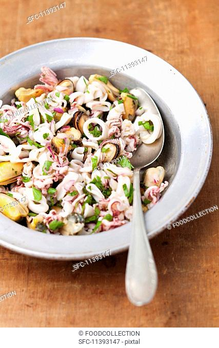 Seafood salad with red onions, parsley, lemon and olive oil