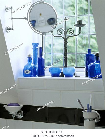 Close-up of collection of blue glass bottles with mirror on stand on windowsill