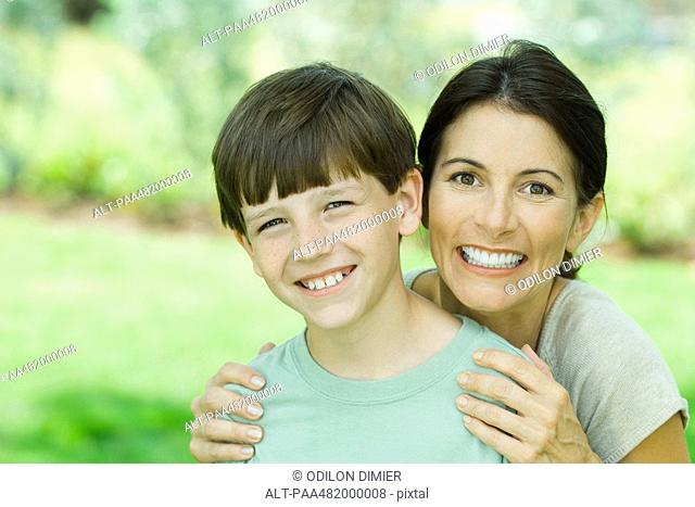 Mother and son smiling at camera together, portrait