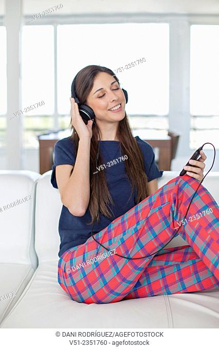 Pretty brunette woman listening to music on the sofa