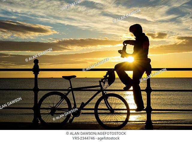 Female mountian biker at sunrise at Seaton Carew on the north east coast of England, United Kingdom