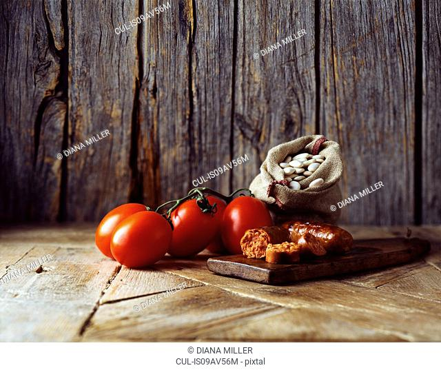 Roma tomatoes on vine, chorizo and butter beans in burlap sack on wooden cutting board