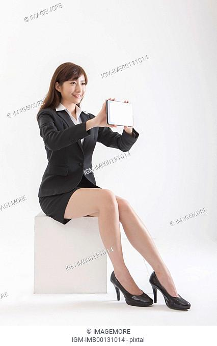 Young business woman sitting and holding touch pad