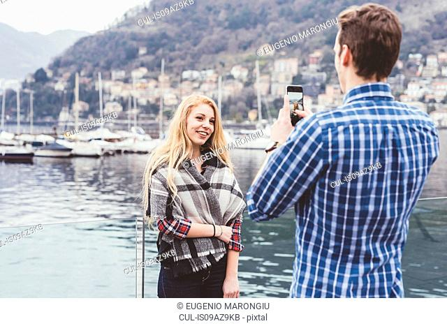 Young man on waterfront photographing girlfriend, Lake Como, Italy