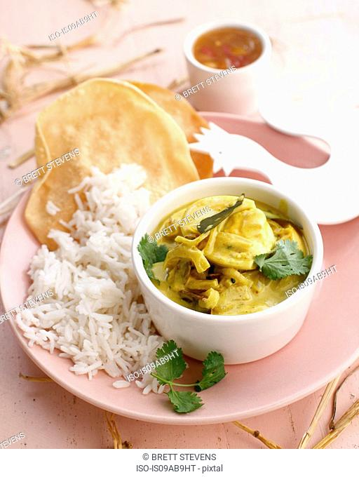 Still life of fresh egg curry with rice and chutney