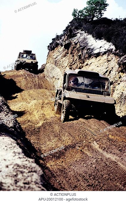 Two off-road all-terraine vehicles travelling down a dirt track