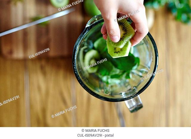Woman holding sliced green kiwi over blender