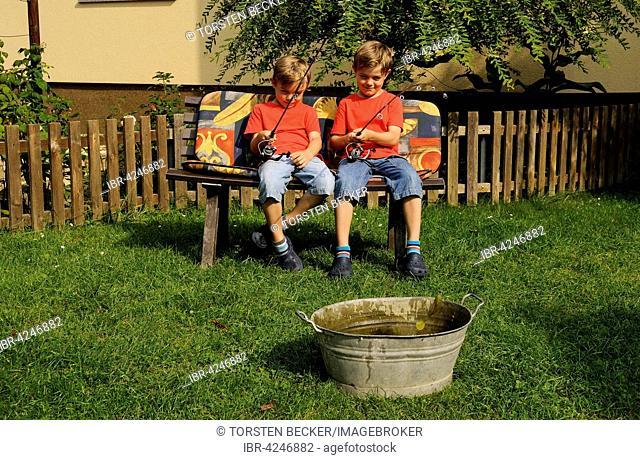 Twins sitting side by side on bench in garden, fishing in bathtub