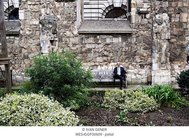 UK, London, senior businessman sitting on bench in a courtyard relaxing