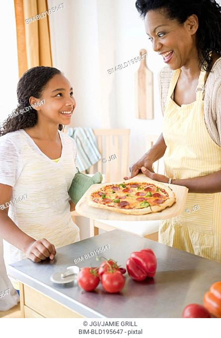 Mother and daughter preparing pizza for dinner