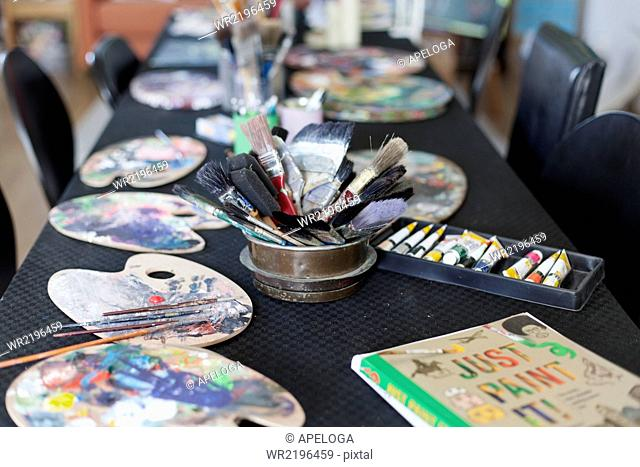 Paint brushes and palettes on table in studio