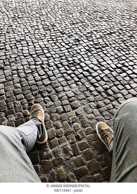 Legs of business casual young man sitting over a cobblestone pavement