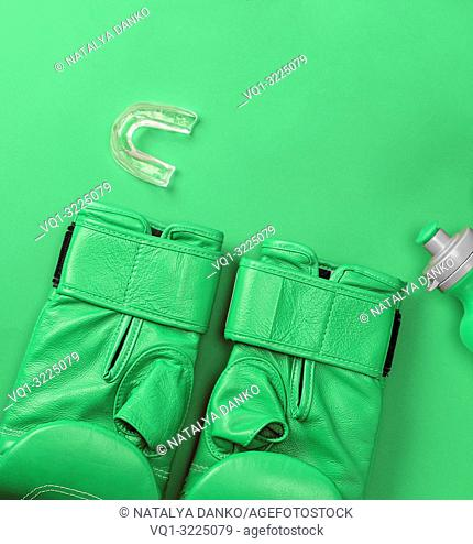 pair of leather green boxing gloves and a water bottle on a background, empty space, abstract sports background