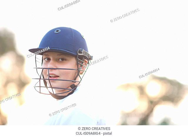 Boy wearing cricket helmet, portrait