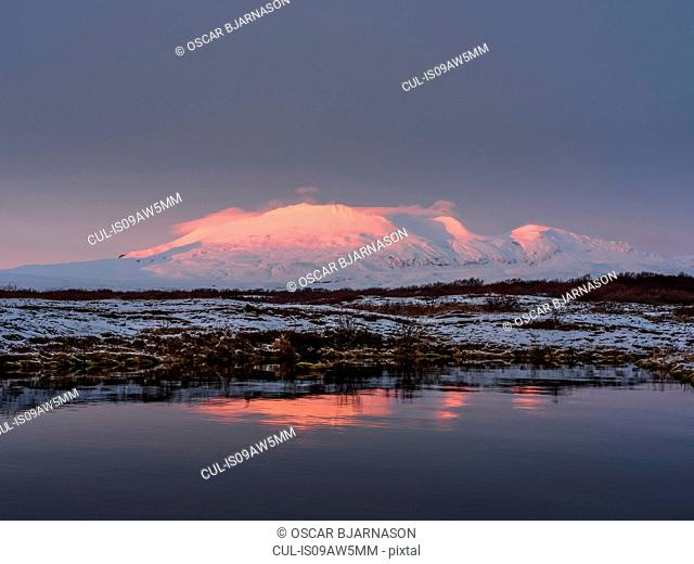 Lake, scrubland and snow covered mountain at sunset, Thingvellir, Iceland