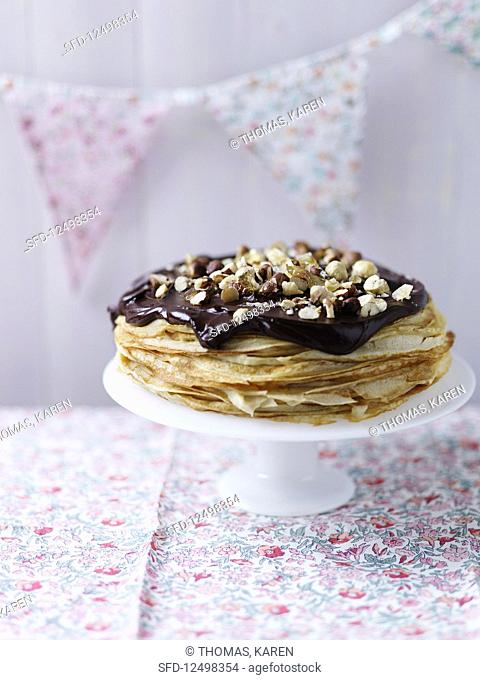 A crepe cake topped with chocolate and hazelnuts
