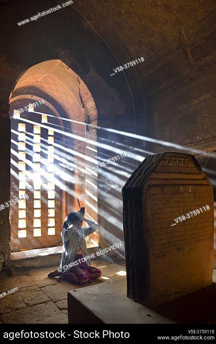 Myanmar, Bagan, Minnanthu, Thin Kan Yone temple, Old lady praying and offering incense to the Buddha