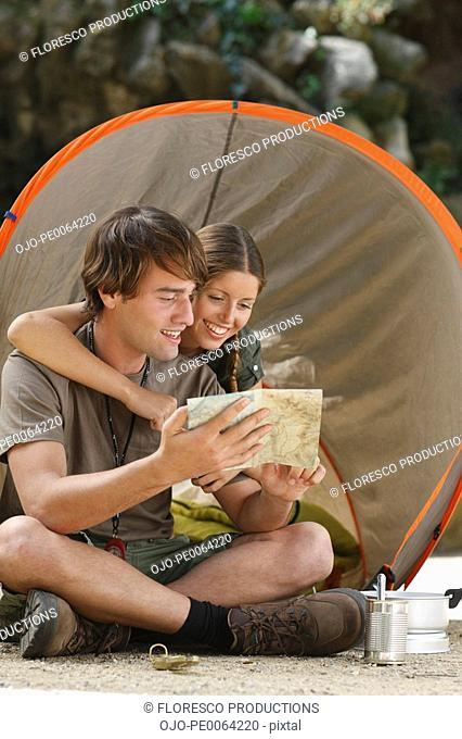 Couple looking at map at campsite