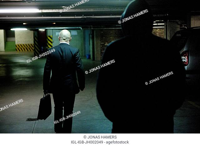 Picture shows a man dressed in suit being followed by a hooded man in a dark parking