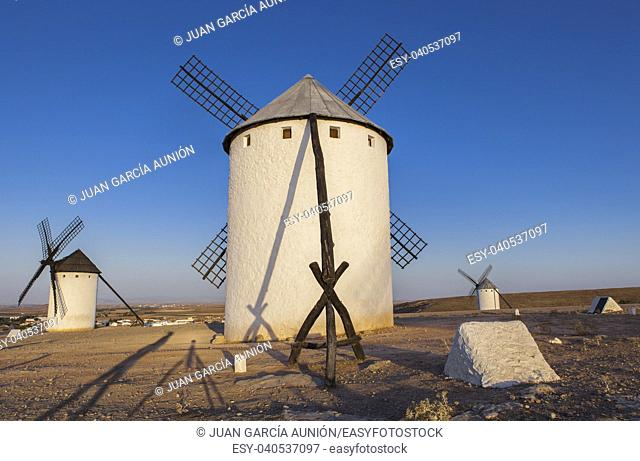 Campo de Criptana windmills at rising. Photographer and camera tripod long shadows on the ground, Spain