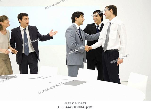 Group of professionals standing beside table, smiling, two shaking hands