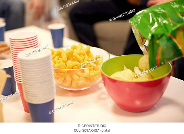 Cropped view of table with disposable cups and bowls of potato chips and snacks