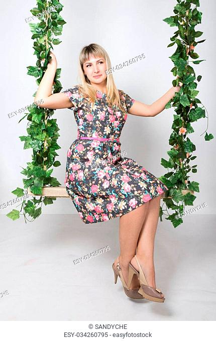 Beautiful young leggy redhaired woman in a long colorful dress on a swing, wooden swing suspended from a rope hemp, rope wrapped vine and ivy