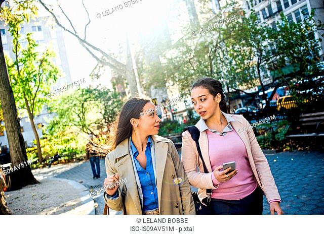 Young adult female twins chatting and walking through city park