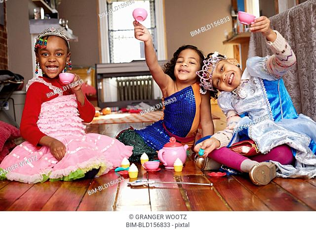Girls playing dress-up and posing at tea party