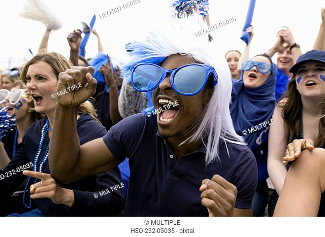 Enthusiastic fan in oversized blue sunglasses cheering