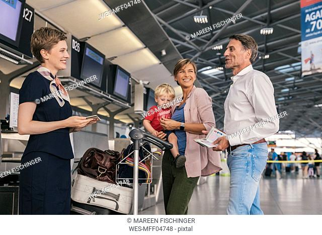 Happy family with airline employee at the airport check-in