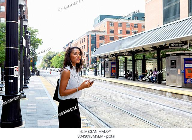 Businesswoman using cellphone in light rail station
