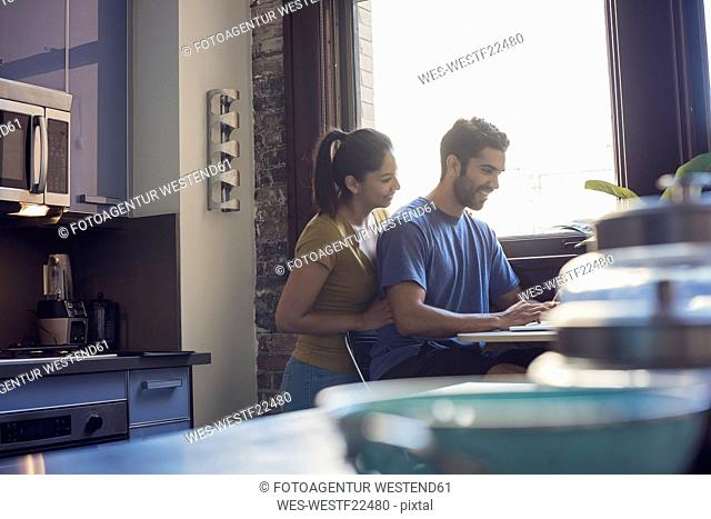 Young couple embracing in kitchen