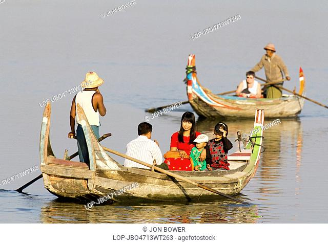 Myanmar, Mandalay, Lake Taungthaman. Tourist pleasure boats plying their trade by U Bein Teak Bridge across Taungthaman Lake in Myanmar