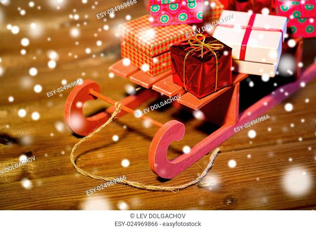 holidays, christmas, presents, new year and celebration concept - close up of many little gift boxes on red wooden sleigh on wooden table