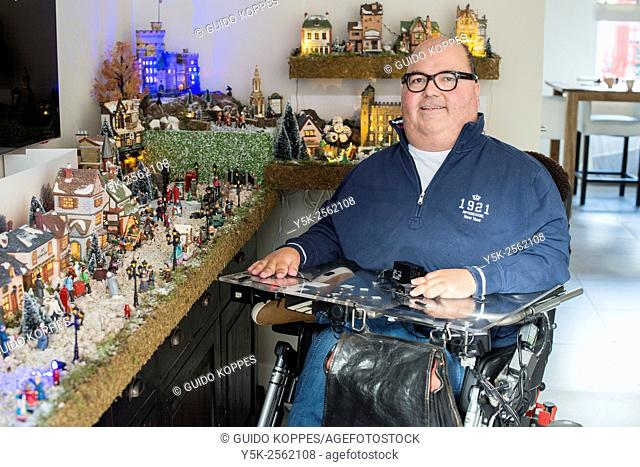 Tilburg, Netherlands. Disabled man in wheelchair due to muscular distrophy posing at home in front of his Dickens Christmas village